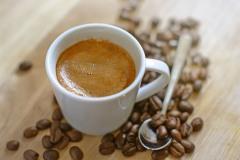Fotografie Cafe: Kaffe Espresso Kaffeebohnen auf Holztisch unscharfer Hintergrund