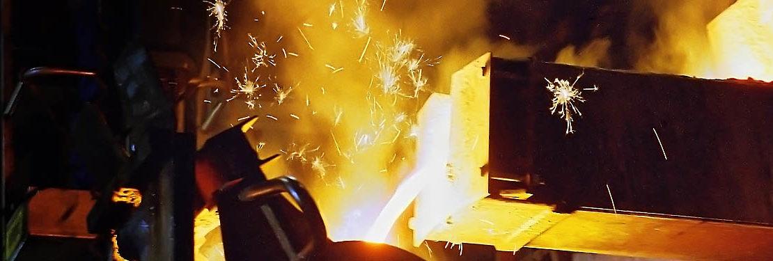 Slidermotiv Hingucker Giessereiindustrie - flüssiges Eisen fließt in einen großen Tigel